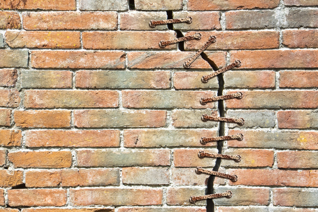 Cracked brick wall with a metal seam